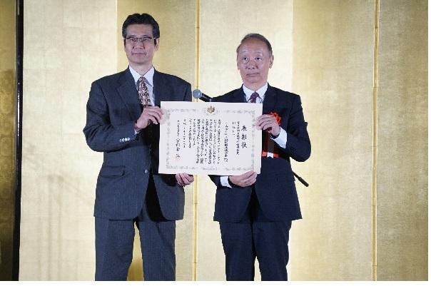 11月19日(月)に行われた表彰式で、宇都宮啓 厚生労働省健康局長(左)から表彰状を受け取る、小林新治 コープデリ連合会副理事長